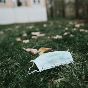 Foto de una mascarilla protectora tendida en el suelo por Tatiana Rodríguez en Unsplash